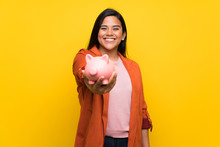 Young Colombian Girl Over Yellow Wall Holding A Piggybank