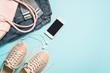 Leinwandbild Motiv Woman fashion cloth set pink shoes, jeans, handbag, smartphone and perfume on blue background.
