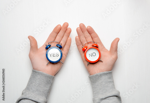 men's hands hold a red and blue alarm clock with the words yes and no Canvas-taulu
