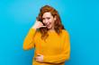 Leinwandbild Motiv Redhead woman with yellow sweater making phone gesture. Call me back sign