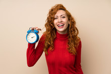 Redhead Woman With Turtleneck Sweater Holding Vintage Alarm Clock