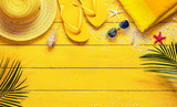 Yellow Summer Background With Beach Accessories And Palm Leaves