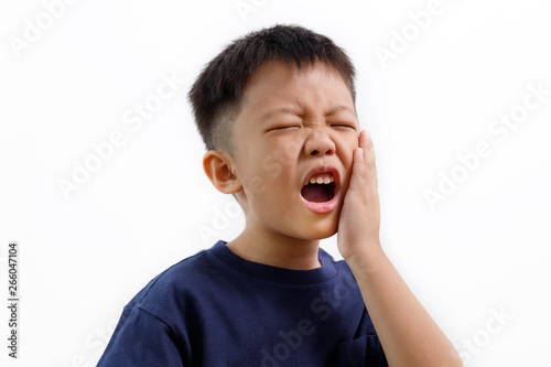 Stampa su Tela  Asian kid suffering from toothache pain, holding his cheek, isolated on white background