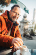 canvas print picture - Outdoor portrait of middle age man wearing eyeglasses and orange winter jacket. Drinking coffe in outdoor cafe
