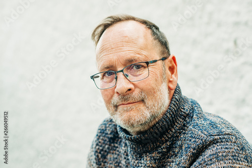 Obraz Outdoor portrait of 50 year old man wearing brown pullover and eyeglasses - fototapety do salonu