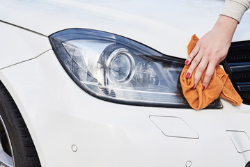 Woman hand clean car headlight with microfiber cloth, close up