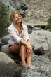 A Smiling young woman relaxing in a mountain creek while on vacation.