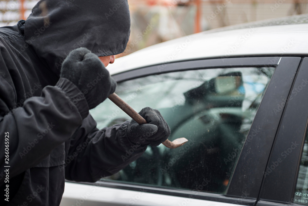 Fototapeta Male thief going to break car window with crowbar. Car theft - thief trying to break into the vehicle
