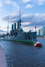 Petersburg, Russia - May 4 2019:Russian Cruiser Aurora In The Mouth Of Neva River In Petersburg Near Nakhimov Naval School In The Evening. The Navy Museum And The Symbol Of Great October Revolution