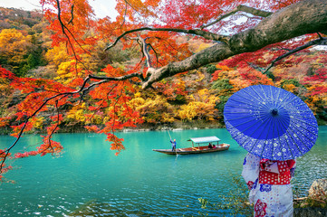 FototapetaAsian woman wearing japanese traditional kimono at Arashiyama in autumn season along the river in Kyoto, Japan.