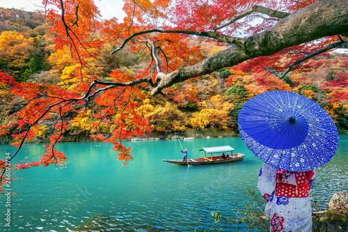 Poster Kyoto Asian woman wearing japanese traditional kimono at Arashiyama in autumn season along the river in Kyoto, Japan.