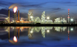 Oil refinery at night with reflection in water - 266076106