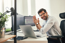 Young And Successful. Happy Bearded Trader In Formal Wear And Eyeglasses Looking At Camera And Smiling While Sitting In His Modern Office.