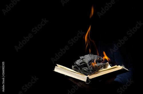 Man holds a burning book. Fototapet
