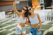 Young women taking selfie with mobile phone outdoor at hot summer day