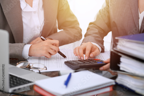 Photo Two female accountants counting on calculator income for tax form completion hands close-up