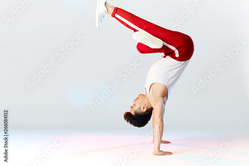 Asian Bboy standing in freeze stunt upside down balancing in air with legs - Street artist breakdancing indoors isolated in studio over white background - 266084132