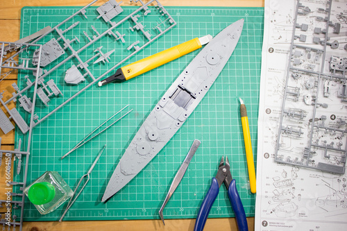 building plastic model WW2 battleship with tools on cutting pad closeup Wallpaper Mural