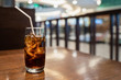 A glass of cola with ice cube on wooden table over blurred restaurant background, refresh drink