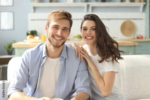 Photo  Portrait of cute young couple sitting in sofa.