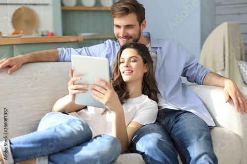 Fototapety, obrazy: Young couple watching media content online in a tablet sitting on a sofa in the living room.