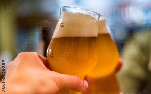 Close-up view of a two glass of beer in hand Wallpaper Mural