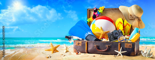 Obraz Beach accessories in suitcase on sand. Family holidays concept - fototapety do salonu