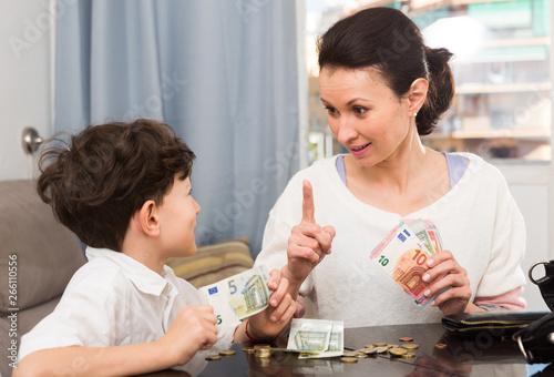 Woman giving money and admonishing boy Canvas Print