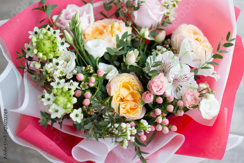 a large bouquet of different flowers of pastel delicate shades: roses, buttercups, eustoma, alstroemeria in bright wrapping paper of pink and white colors, top view