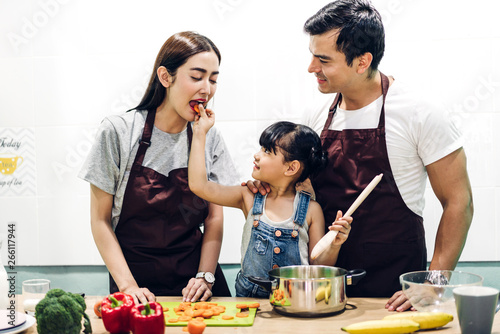 Foto  Happy family father and mother with daughter cooking and preparing meal together