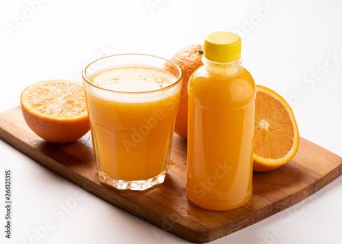 Fototapeta Orange juice in bottle with slices of orange on wooden board over white background obraz