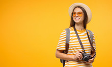 Horizontal Banner Of Smiling Young Female Traveller Holding Camera, Isolated On Yellow Background With Copy Space