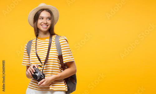 Horizontal banner of smiling young female tourist holding camera, isolated on yellow background with copy space