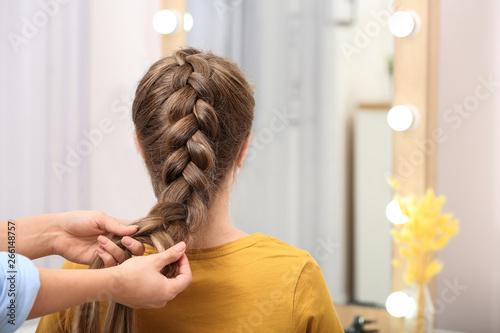 Obraz Professional coiffeuse braiding client's hair in salon - fototapety do salonu