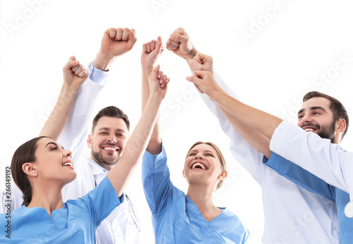 Obraz Team of medical doctors raising hands together on white background. Unity concept - fototapety do salonu