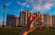 A Hand Is Holding A Wooden Dollar Sign On The Background Of A New Building Apartment Building
