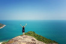 Young Woman Worth Of Grief And Looks At Beautiful Bright Blue Sea, Back View. Hands Up. Adventure Wanderlust Lifestyle
