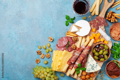 Italian appetizers or antipasto set with gourmet food on blue table top view Wallpaper Mural