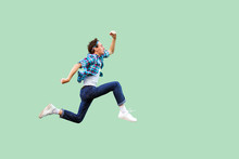 Jump To The Success. Full Length Profile Side View Of Active Young Man In Casual Blue Checkered Shirt And Headband Running Very Fast Or Jumping. Indoor Studio Shot, Isolated On Green Background.