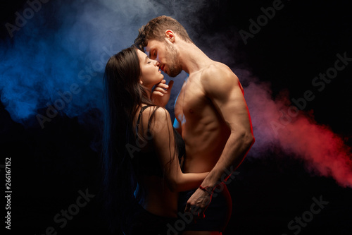 Obraz na plátně passionate couple kissing while standing face to face, isolated on black background