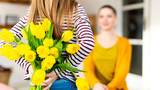 Happy Mother's Day or Birthday Background. Adorable young girl surprising her mom with bouquet of yellow tulips. Family celebration concept. - 266171961