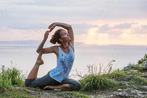 Fototapeta  Caucasian woman practicing yoga at seashore