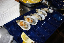 Fresh Oysters With Some Lemon And Sauce Served On A Blue Plastic Plate On The Food Market In Melbourne, Australia