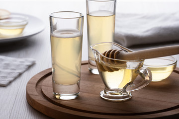 honey and mead in a glass on a wooden stand