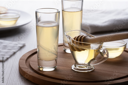 Photo honey and mead in a glass on a wooden stand