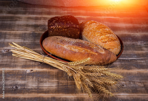 Foto op Aluminium Brood Fresh fragrant bread on a wooden table at sunset. Homemade hot pastry with.