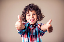 Kid Boy Shows Thumbs Up Sign And Smiles. Children And Emotions Concept