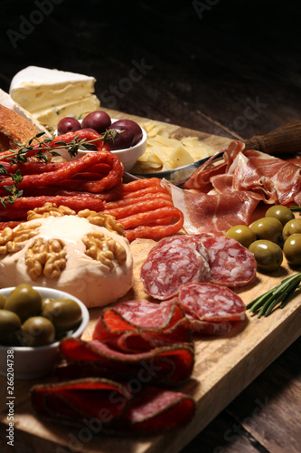 Canvas Prints Spices Cutting board with prosciutto, salami, cheese,bread and olives on dark wooden background