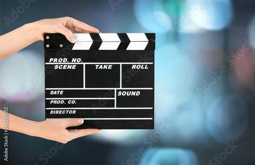 Cinema clapperboard in female hands on blue bokeh background Wallpaper Mural