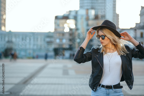 fototapeta na drzwi i meble Outdoor fashion portrait of a pretty blonde woman wearing hat and mirror sunglasses. Space for text